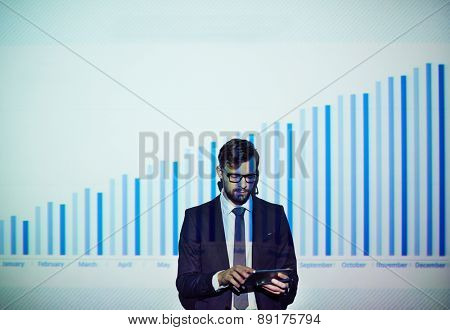 Serious businessman using touchpad on background of chart on the wall