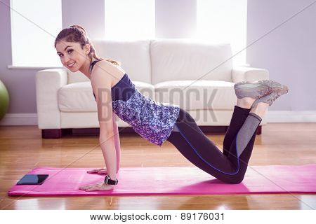 Fit woman doing press up on mat at home in the living room