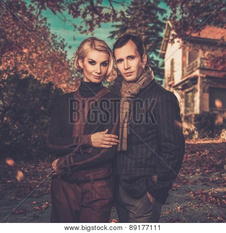 Elegant couple against country house on autumn day