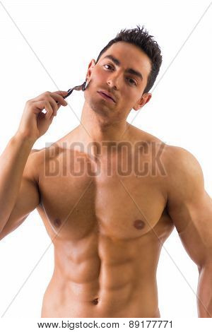 Shirtless muscular man shaving face with manual razor