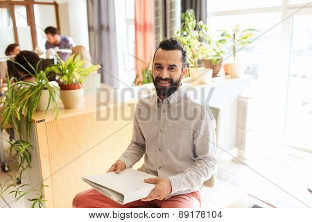 business, startup and people concept - happy businessman or creative male office worker with folder