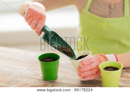 people, gardening, seeding and profession concept - close up of woman hands with trowel burying seeds in soil