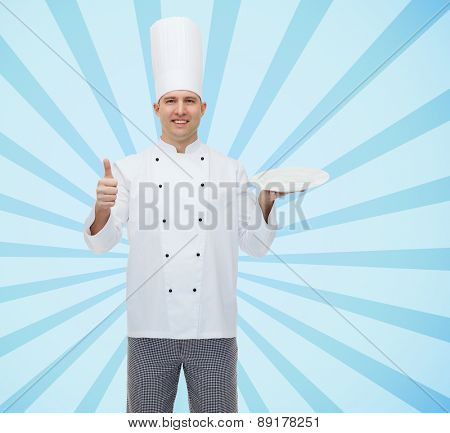 cooking, profession, advertisement and people concept - happy male chef cook holding something on empty plate and showing thumbs up over blue burst rays background