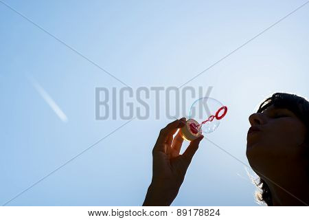 Woman Blowing Bubbles Against A Blue Sky