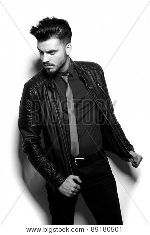Young handsome business man looking down while pulling his jacket, balck and white image.