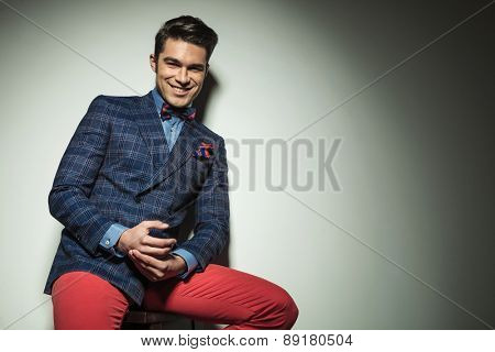 Happy young fashion man sitting on a chair while leaning on a grey wall, he is holding his hand together.