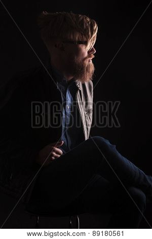 Side view image of a hipster man looking away from the camera while sitting on a chair.