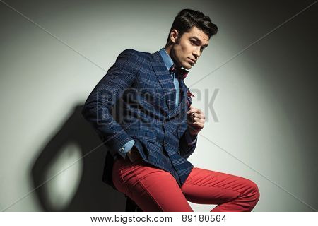 Side view of a handsome fashion man looking down while sitting on a chair with his hand in pocket.