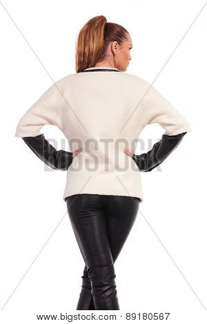 Rear view of a young fashion woman standing with her legs crossed while looking away.
