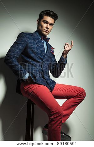 Young handsome fashion man sitting on a stool pointing up.
