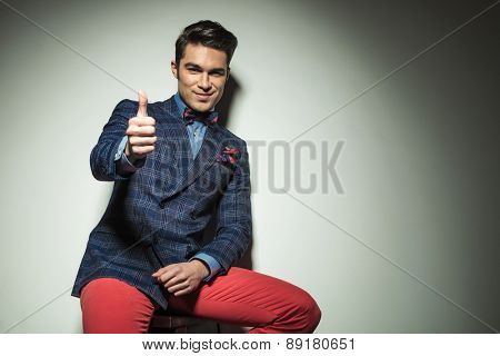Handsome casual fashion man sitting on a chair while showing the thumbs up gesture.