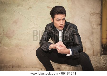 Casual fashion man holding his hands together while looking away from the camera.