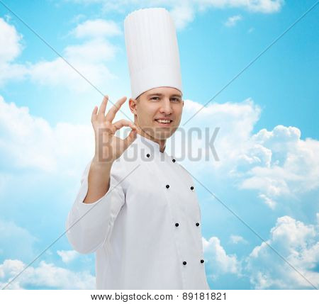 cooking, profession, gesture and people concept - happy male chef cook showing ok sign over blue sky with clouds background