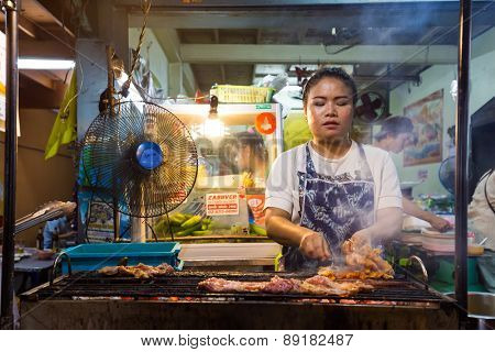 BANGKOK,THAILAND,FEBRUARY 16,2015: A woman is cooking chicken brochettes on barbecue in a small restaurant of the Sukhumvit Soi 38 in Bangkok,Thailand