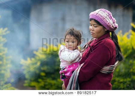 MAE KLANG LUANG, THAILAND, DECEMBER 31, 2014: A Karen tribe woman in traditional cloth is holding her kid in the village of Mae Klang Luang in the Doi Inthanon national park near Chiang Mai, Thailand