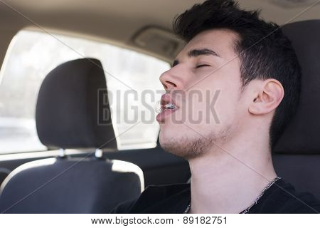Young man sleeping at the wheel driving his car