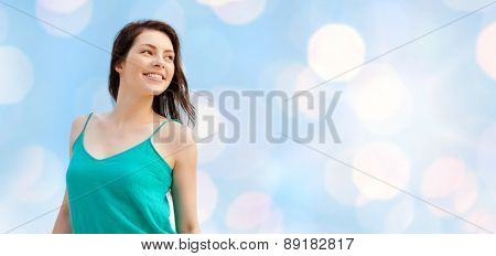 summer holidays, people, youth and happiness concept - happy girl or young woman looking aside over blue lights background