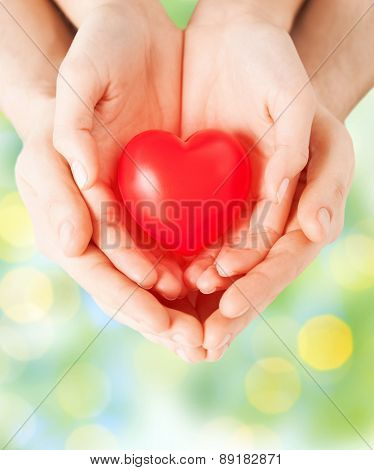 health, love and relationships concept - close up of couple hands with big red heart over green lights background