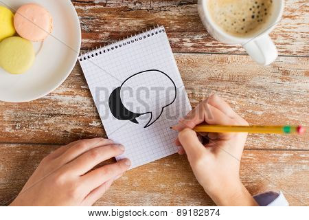business, education and people concept - close up of female hands with pencil, coffee and cookies drawing text bubble to notebook on table
