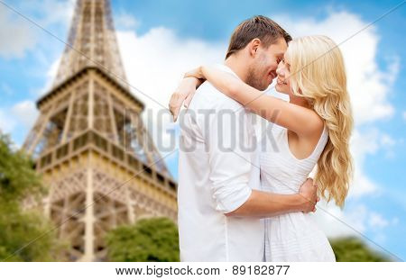 travel, tourism, people, love and dating concept - happy couple hugging over eiffel tower in paris background