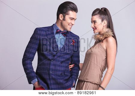 Young happy fashion couple looking at each other while smiling.