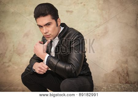 Side view of a handsome young fashion man holding his thumb to the chin while sitting.