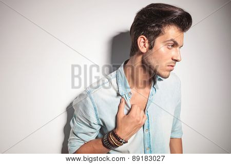 Side view of a young fashion man leaning on a wall while pulling his collar.