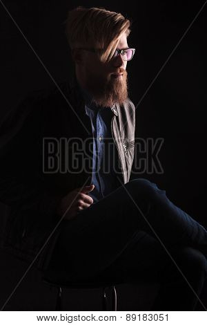Blond hipster man sitting oo a chair on black studio background while fixing his jacket.