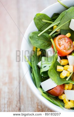 healthy eating, dieting, vegetarian kitchen and cooking concept - close up of vegetable salad bowl at home