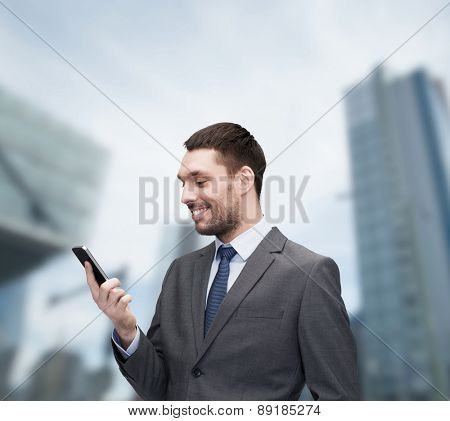 business, technology, internet and education concept - friendly young smiling businessman with smartphone