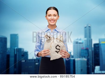 business, people, finances, investments and banking concept - young businesswoman holding money bags with euro over city background