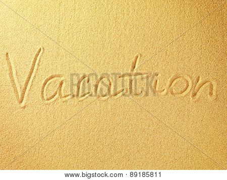 The word Vacation is written on a sand background