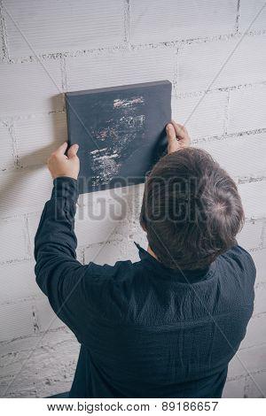 Painter artist hanging up finished modern artwork