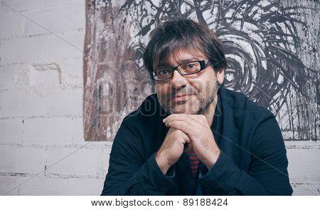 Painter artist posing in front of modern artwork