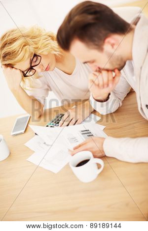 A picture of a worried couple with documents at home