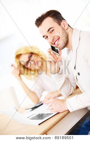 A picture of a young happy couple with documents at home