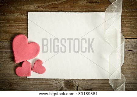 The Piece Of Paper Lying With Hearts And Ribbon On A Wooden Background
