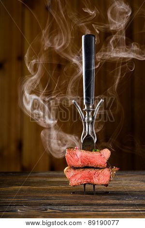 Sliced Beef Steak On A Fork On The Wooden Table