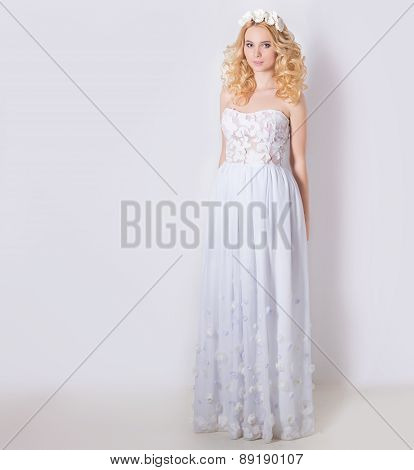 beautiful lovely gentle elegant young blond woman in a white sundress chiffon and curls, and a wreat