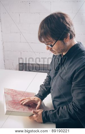 Painter artist reviewing his finished modern artwork