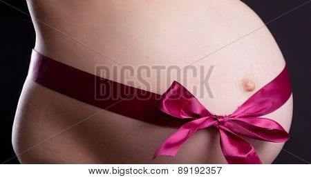 Pregnancy. Abdomen. Red Ribbon. Black Background