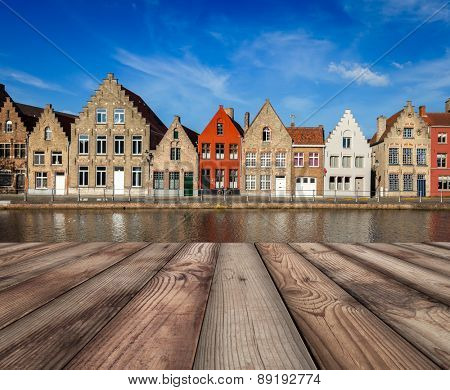 Wooden planks table with typical European Europe cityscape view -  canal and medieval houses in background. Bruges (Brugge), Belgium