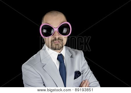 businessman wearing big funky pink glasses isolated on black background