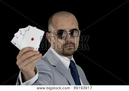 man in business suit holding four aces poker cards in his hand isolated on black background