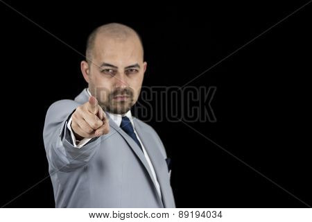 successful businessman in suit pointing at you isolated on black background