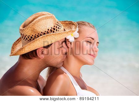 Portrait of handsome man kissing his nice young wife, closed eyes of pleasure, enjoying each other on the beach, summer vacation on exotic resort