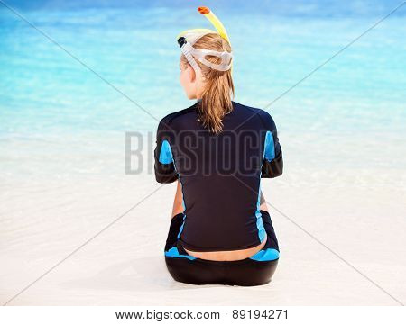 Back side of calm diver girl sitting on seashore, wearing snorkeling equipment and resting on the beach, summer adventure and traveling concept