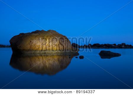Uniquely Lit, Dramatic Rocky Island In A Tranquil Sea