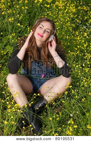 Beautiful Young Girl With Headphones In The Flowers