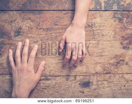 Male And Female Hand On Wooden Table